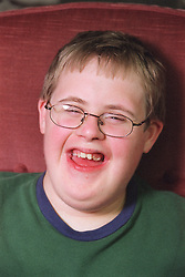 Portrait of boy with Downs Syndrome laughing,