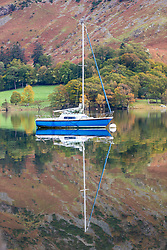 © Licensed to London News Pictures. 15/10/2018. Glenridding UK. A boat reflects in to the still water of Ullswater lake at Glenridding this morning in Cumbria. Photo credit: Andrew McCaren/LNP
