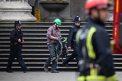 © Licensed to London News Pictures. 19/05/2016. London, UK. A climber who scaled the building being escorted from the premises by police. A Greenpeace protest by Greenpeace at the British museum which has closed the museum. Greenpeace climbers have scaled pillars at the museum, erecting banners protesting against BP sponsorship of Sunken Cities: Egypts - Lost Worlds exhibition at the museum. ‎Photo credit: Ben Cawthra/LNP