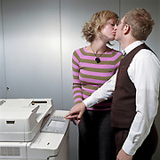 Businessman and businesswoman kissing while using photo copier