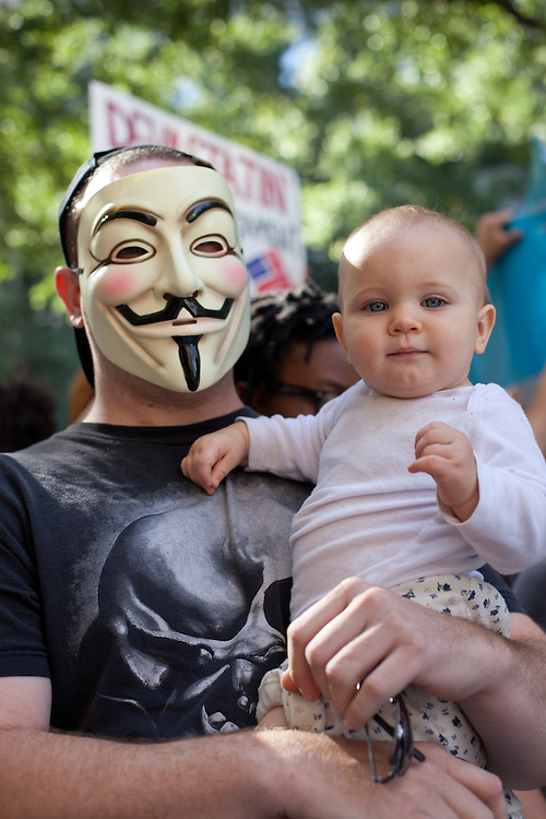 A man with a Guy Fawkes mask holds his child during the Occupy Charlotte protest in front of BOA headquarters in uptown.
