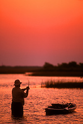 Stock photo of the silhouette of a man wade fishing in the bay while tethered to his kayak at sunset