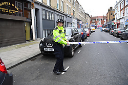 © Licensed to London News Pictures. 31/12/2018. London, UK. A police officer redirects traffic tapes off crime scene where man in his 30s was left fighting for his life after being stabbed on Fulham Palace Road in an unprovoked attack in the early hours of New Years Eve. Police have arrested 39 individuals at a party  at a near by address where the assailant ran to following the attack according to eye witnesses. Photo credit Guilhem Baker/LNP