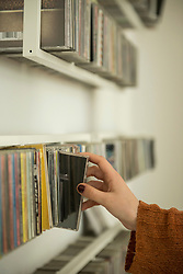 Close-up of a woman hand picking a cd from shelf, Munich, Bavaria, Germany