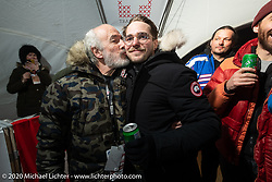 Custom bike builder Bertrand Dubet gives his team mechanic Simon Pitelet a big kiss at the wrap party after the Baikal Mile Ice Speed Festival. Maksimiha, Siberia, Russia. Saturday, February 29, 2020. Photography ©2020 Michael Lichter.