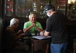 1920 Tavern employee Shane Goode (right) delivers drinks to Bart Van Linden and his mother, Sabine Van Linden, at the Roswell restaurant Monday, April 27, 2020. Photo by Steve Schaefer/Atlanta Journal-Constitution/TNS/ABACAPRESS.COM