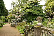 Classcal stone stairs decorated with an urn and round finials leading to a gravel path and the Cornus collection at Newby Hall, Ripon, North Yorkshire, UK