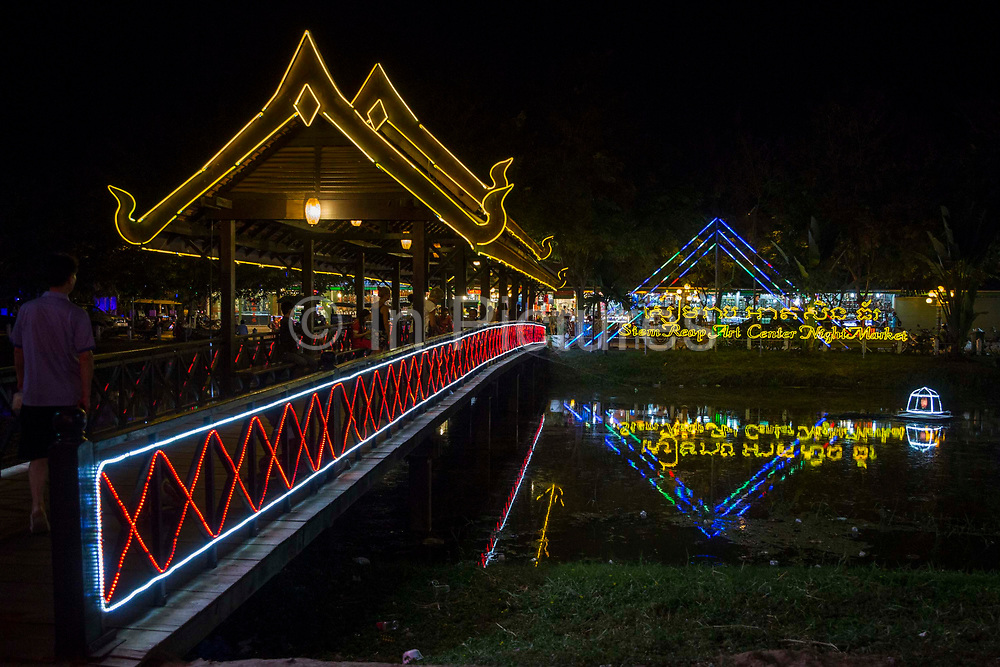 A traditional wooden bridge over Siem Reap River leading to the Siem Reap Art Centre Night Market lit-up and decorated in neon lights.  The market sells souvenirs, art work and carvings. The market opened in 2012.
