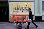 Man with transporting trolley walks past construction barrier and Libyan postal stamp mural image.