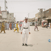 Policeman named Imam Bux regulates traffic under 50 degrees heat. He gets paid 20.000 Rupees, 125 USD per month.