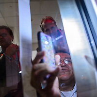110414       Cable Hoover<br /> <br /> Brian Lee uses his phone to illuminate the ticker tape election results Tuesday evening at the McKinley County Courthouse.