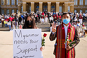 "06 MARCH 2021 - DES MOINES, IOWA: A couple from the Burmese community in Iowa at a protest against the military coup in Myanmar. The man, dressed in traditional Chin dress (a Burmese ethnic minority) is marking the three finger ""Hunger Games"" salute. The so called ""Hunger Games salute,"" from the movie ""The Hunger Games"" is used by Burmese to protest the coup. About 300 members of the Burmese community in Iowa gathered at the State Capitol in Des Moines Saturday to protest against the military coup that deposed the popularly elected government of Aung San Suu Kyi and continuing military oppression in Myanmar. There are about 10,000 people in Iowa's Burmese community.            PHOTO BY JACK KURTZ"