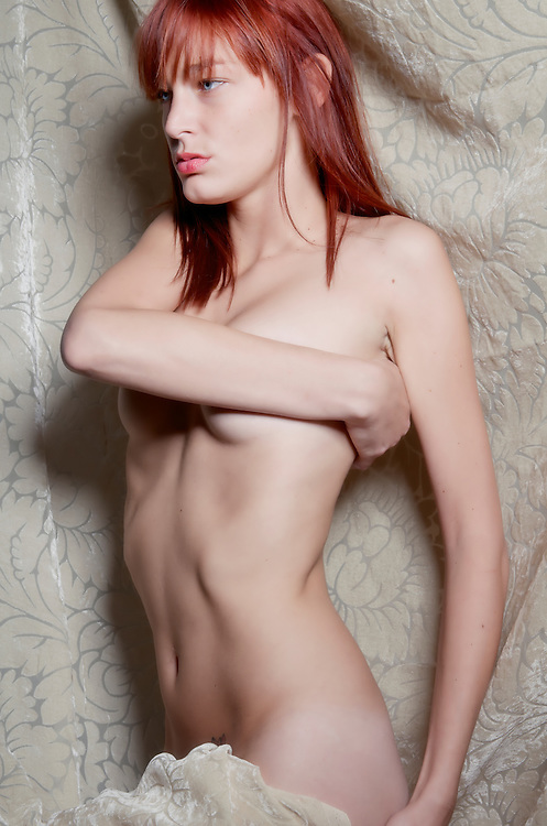Sensual readhair young model posing nude with drape.