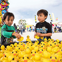 Brothers Josiah Bia, 4 and Elijah Bia, 5, pick rubber duckies from the Lucky Duck Pond carnival game Thursday, Sept. 6, 2018 at the Navajo Nation Fair in Window Rock, Arizona.