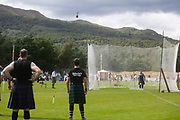 Highland Games, 3rd of August 2019, Newtonmore, Scotland, United Kingdom. Strong men look on as one of their pompetitors throw the weight. The Highland Games is a traditional annual event where competitors compete as strong men, runners, dancers, pipers and at tug-of-war. The games go back centuries and are happening through-out the summer across Scotland. The games are both an important event locally and a global tourist attraction.