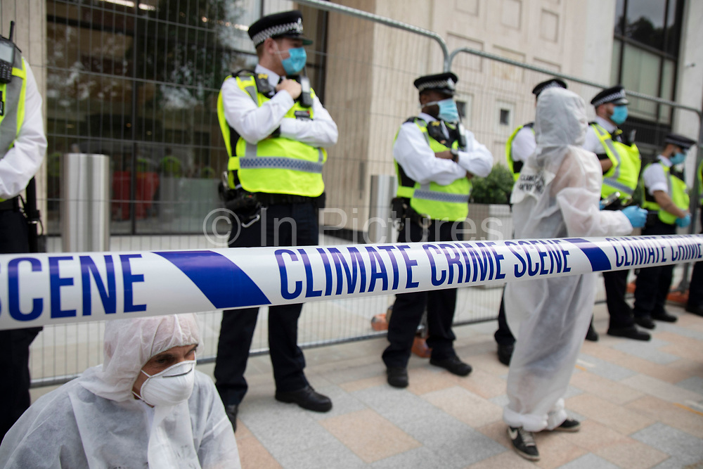 Extinction Rebellion 'crime scene investigators' in white suits and masks put up climate crime scene tape to investigate areas of ecocide in a performance outside the Shell building during the Shell Out protest on 8th September 2020 in London, United Kingdom. The 20 investigators were protesting at the ongoing extraction of fossil fuels and the resulting environmental record. Extinction Rebellion is a climate change group started in 2018 and has gained a huge following of people committed to peaceful protests. These protests are highlighting that the government is not doing enough to avoid catastrophic climate change and to demand the government take radical action to save the planet.