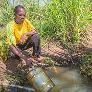 CAPTION: Fidelis fills his watering can in the family's 'dimba' (irrigated garden). This is small scale irrigation farming, where the crops are watered not by treadle pumps but using cans. There is a lot of watering work to do at this time of year. LOCATION: Nsanja-Seze, Vila Ulongwe area, Angonia District, Tete Province, Mozambique. INDIVIDUAL(S) PHOTOGRAPHED: Fidelis Dickson.