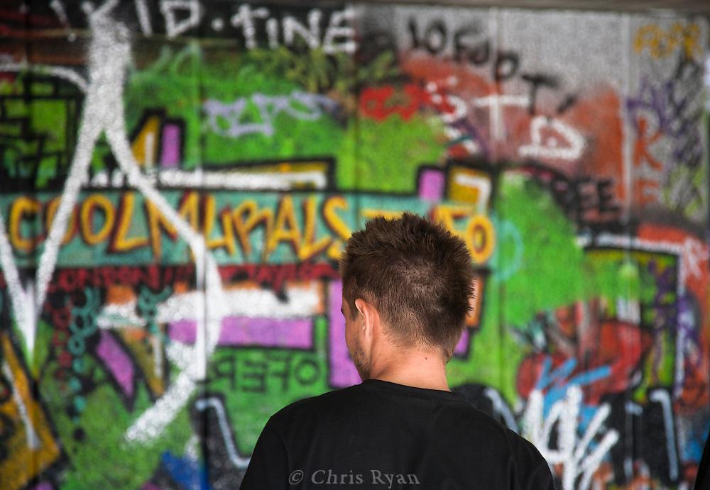 Biker in front of grafitti at a skate park in London, United Kingdom