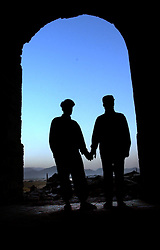 KABUL,AFGHANISTAN - SEPT. 12:  Two Afghan soldiers hold hands as the sun sets near the destroyed Presidential Palace in Kabul, Afghanistan September 12,2002. (Photo by Ami Vitale/Getty Images)