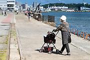 senior woman walking with pet dog in stroller