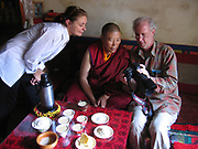 Peter Menzel, photojournalist and co-author of the book What I Eat: Around the World in 80 Diets shows a monk his food portrait. Faith D'Aluisio looks on.