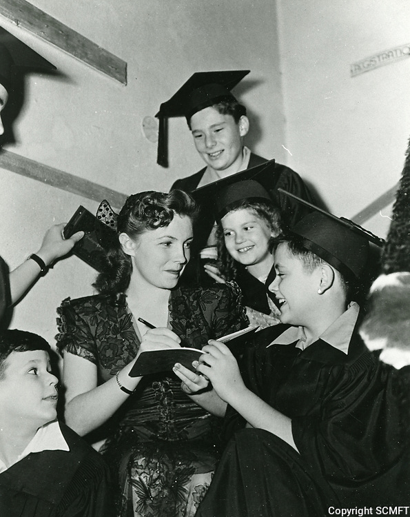 """1943 Actress, Joan Leslie signs autographs for the members of the """"Quiz Kids"""" at the Hollywood Canteen."""