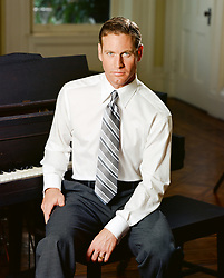good looking man in a shirt and tie sitting by a piano