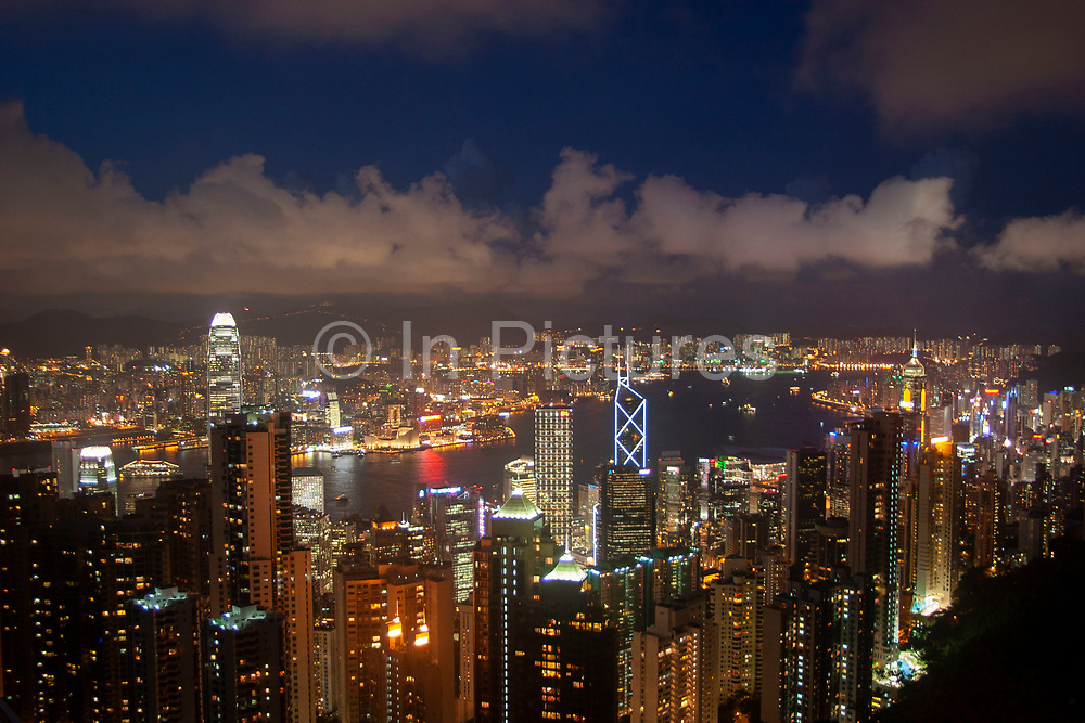Evening view from Victoria Peak in Hong Kong, China. From this classic viewpoint the entire view across Hong Kong Harbour can be seen. The view sweeping down through Mid-levels to Central, along to Causeway Bay, all the way along Hong Kong Islands coast across North Point, Quarry Bay to Wan Chai. Also over the water we see the Chinese mainland area Kowloon. A deep blue Hong Kong sky forms a backdrop for the forming clouds which are lit up by Two International Finance Centre, Hong Kongs tallest building at 415m.