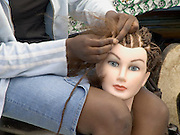 girl practicing braiding hair on a mannequins head