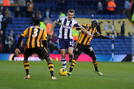 West Brom's Gareth McAuley © goes past Hull city's Yannick Sagbo ® and Maynor Figueroa. Barclays Premier league, West Bromwich Albion v Hull city at the Hawthorns in West Bromwich, England on Saturday 21st Dec 2013. pic by Andrew Orchard, Andrew Orchard sports photography.