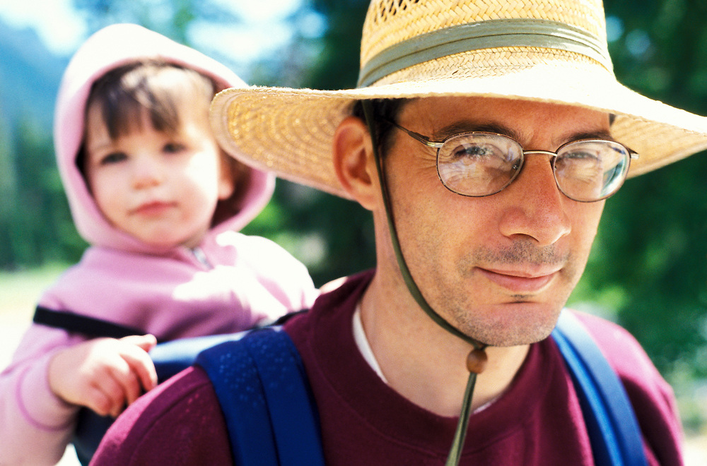 A man carrying his child in a backpack carrier while hiking in the Cascade mountains of Washington, USA.
