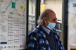 © Licensed to London News Pictures. 20/03/2021. London, UK. A man wearing a face covering at a bus stop in north London. The UK government fears a rise in Covid-19 cases in the UK amid a new coronavirus surge across Europe, which has led to a number of European countries back into lockdown. Photo credit: Dinendra Haria/LNP