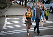 A young couple holding hands crosses the street while looking at the camera in downtown Seattle, Washington, USA