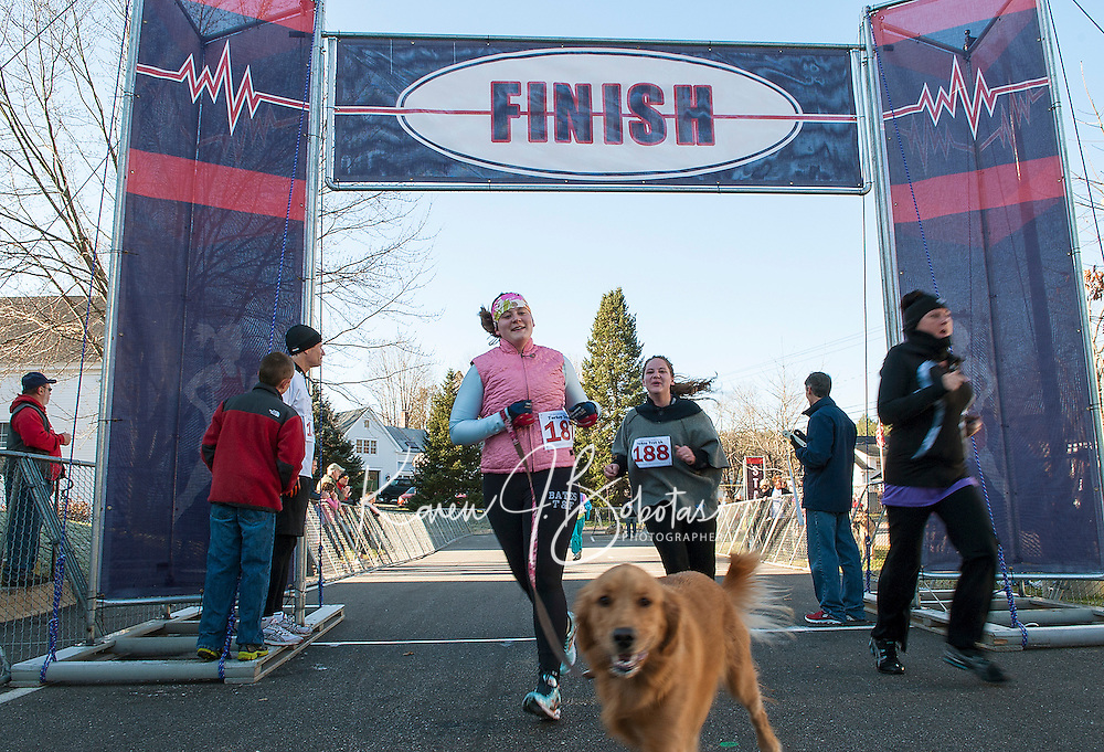 Chloe leads the way as Sarah Ellen and Lucille Godek cross the finish line of Gilford Youth Center Thanksgiving Day Turkey Trot 5k Thursday morning.  (Karen Bobotas/for the Laconia Daily Sun)
