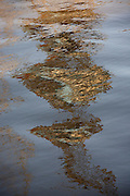 Refracted and broken lines of a dock crane shimmering on the waters of the River Thames at Industrial Northfleet, Kent
