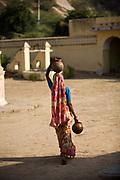 A woman carrying water pots past the cenotaphs of the Maharajahs at the Royal Gaitor (Gatore ki Chhatryan), Jaipur, India