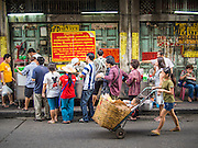 11 SEPTEMBER 2013 - BANGKOK, THAILAND:  A woman pushes a basket with her baby in it past people lined up and waiting to be served at a curry stand in the Chinatown section of Bangkok. Thailand in general, and Bangkok in particular, has a vibrant tradition of street food and eating on the run. In recent years, Bangkok's street food has become something of an international landmark and is being written about in glossy travel magazines and in the pages of the New York Times.        PHOTO BY JACK KURTZ