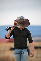 cowboy with a guitar over his shoulder on a ranch