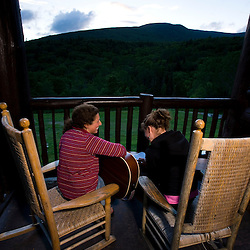 Two young women sing on the porch at the Dartmouth Outing Club's Moosilauke Ravine Lodge at the base of Mount Moosilauke in new Hampshire's White Mountains. (MR)