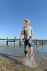 Boy splashing water with his feet, smiling, Bavaria, Germany