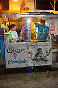 Local food stall cart, selling Churros husband and wife business, standing at their stall. Cuban locals attend a Rodeo in Ciego de Avila province, Cuba.