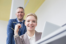 Portrait of colleagues having meeting in office, smiling
