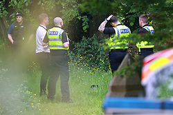 © Licensed to London News Pictures. 03/06/2021. Rochdale, UK. A police officer's helmet is seen on the ground surrounded by officers at the scene. Emergency services on Foxholes Road in Rochdale where police are seen outside All Saints Hamer and Christ Church Healey Vicarage . It's understood that a woman was found dead in a brook close to the scene this afternoon (Thursday 3rd June 2021). Photo credit: Joel Goodman/LNP