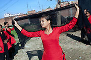"Afreen, 17, a member of the Red Brigades, is performing during a street play promoting awareness about women's condition in India, on the streets of Madiyaw colony, Lucknow District, Uttar Pradesh. The Red Brigades are a group of young women led by Usha, 25, who after an attempted rape began talking about abuse with her students, aged around 14 to 18 years old. Usha founded the Red Brigades in November 2010. They perform in self-written plays on gender equality around villages and cities, take part to protests and also teach self-defence classes. Most of the girls in the group have experienced some kind of abuse in their past. They sing words such as ""all sisters are breaking all the rules, boundaries, come to bring a new world, change will come,"" and ""for how long do we have to go through this?"" and ""the country has freedom, but girls do not have freedom."""