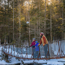 A couple and their daughter on a suspension bridge that crosses the Hudson River near its source in New York's Adirondack Mountains. Upper Works Trail, East River Trail. Tahawus Tract, Newcomb, New York.