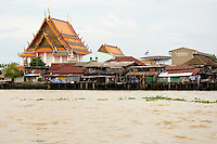 Wat Thong Noppakhun with water front huts along the banks of the Chao Phraya river Bangkok Thailand