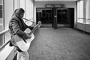 01 OCTOBER 2020 - DES MOINES, IOWA: RANDY KONG, a Des Moines busker, performs in an empty skywalk in downtown. Kong said the pandemic has devastated his income. There are much fewer people working downtown and the ones that are don't stop to listen to him or drop money into his guitar case. The economy in downtown Des Moines is still feeling the affects of the COVID-19 shutdown ordered in March. Seven months after the shutdown, employers still have their workers working from home. Restaurants, barbershops, and retail are feeling the impact. Many have closed or cut back on workers and hours.       PHOTO BY JACK KURTZ