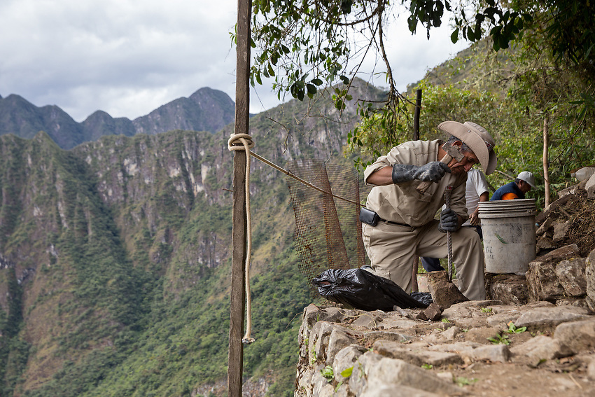 Upon arriving at Machu Picchu a man is seen making repairs to one of the ancient pathways.