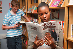 Students in library looking at books.
