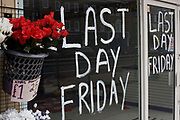 Last Day Friday notice for now closed Card Warehouse business in Bromley High Street, a victim of the UK recession. Poinsettias sit in a plastic bucket, each selling for £1.25. Around a recession-bled Britain, high-street businesses have been going bust in their thousands. Britain has now endured eight recessions since the Second World War. No two recessions are alike, and that applies to the current slowdown also. It has been caused by a shock to the availability of credit, a massive build up of debt. The number of people out of work currently stands at almost two million. Given the rate at which the economy is deteriorating this could easily be above three million. From a continuing piece of work about windows and urban messages, the picture is from the project of closed business windows: 'Bust - the Art of Recession'.